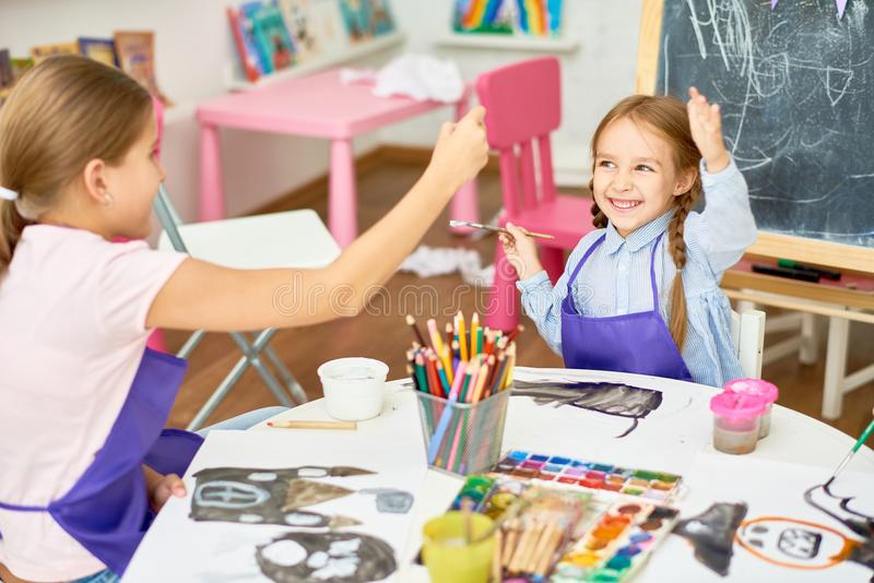 Girls Having Fun in Art Class. Portrait of two little girls enjoying art and craft lesson in development school and having fun royalty free stock image