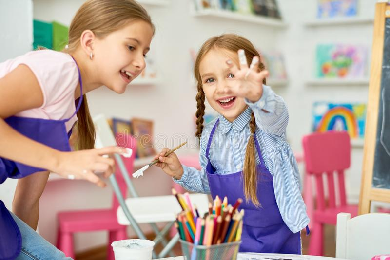 Girls Having Fun in Art Class. Portrait of two little girls enjoying art and craft lesson in development school and smiling happily to camera showing hands in royalty free stock images
