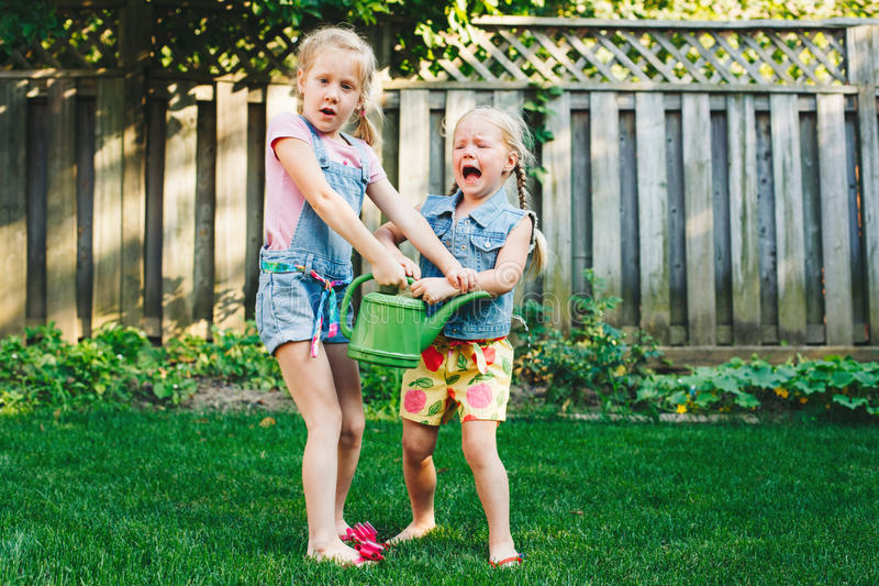 Two little girls sisters having fight on home backyard royalty free stock image