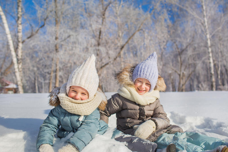 Portrait of two little girls sit and smile in a winter day stock image