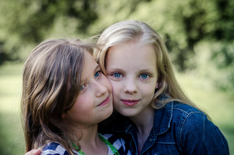 Portrait of two long haired preteen girls while smiling. stock photos