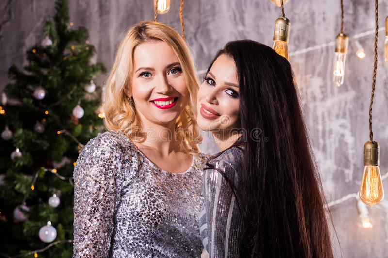Portrait of two lovely pretty women in sparkly dresses hugging and looking at camera isolated over Christmas tree. New Year, holiday, celebration, winter stock images