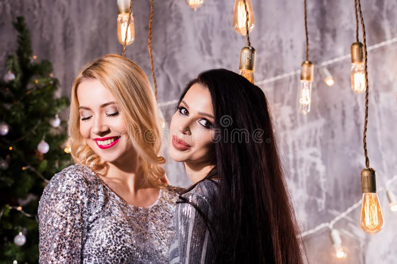 Portrait of two lovely pretty women in sparkly dresses hugging and looking at camera with a smile. Christmas decoration,. Celebration, happiness, new year royalty free stock photography