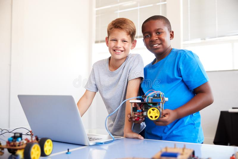 Portrait Of Two Male Students Building And Programing Robot Vehicle In School Computer Coding Class royalty free stock photos
