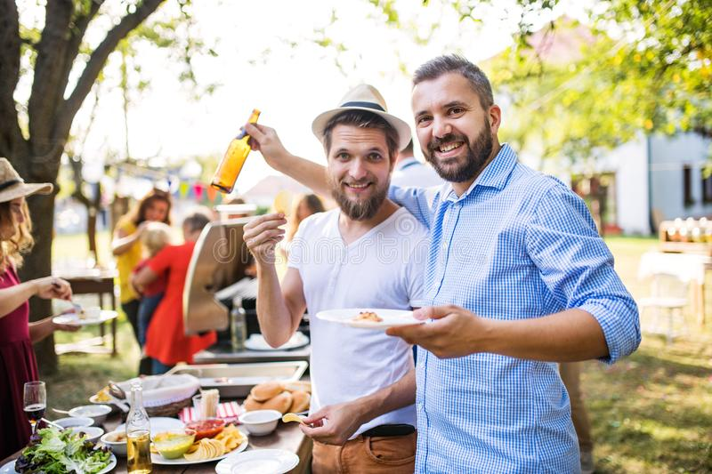 Portrait of two men on a family celebration or a barbecue party outside in the backyard. stock photo