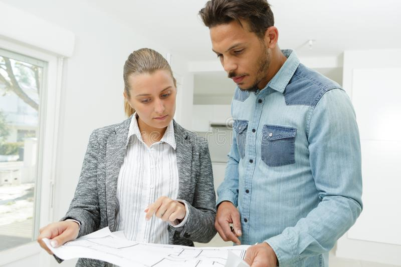 Portrait two modern business people holding plan stock images