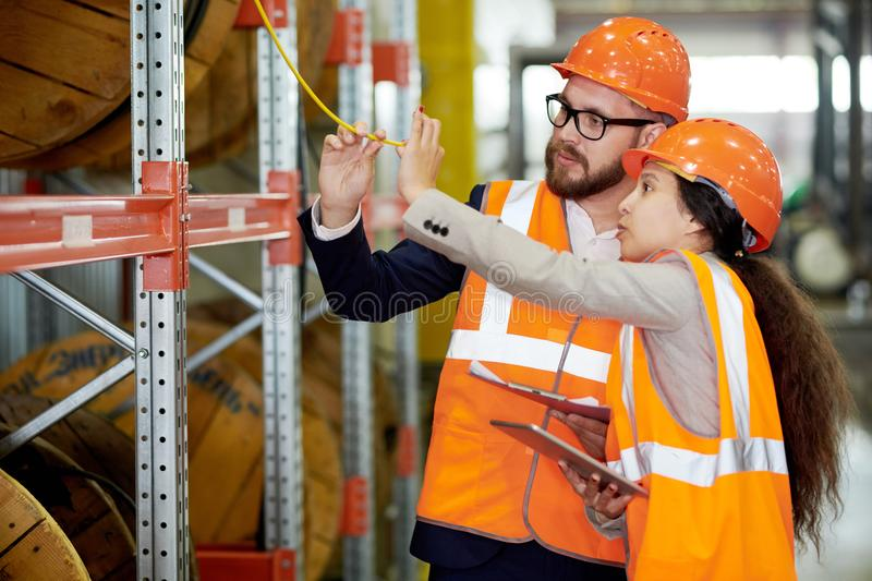 Quality Control. Portrait of two modern factor workers wearing hardhats doing inventory in production warehouse, copy space royalty free stock photography
