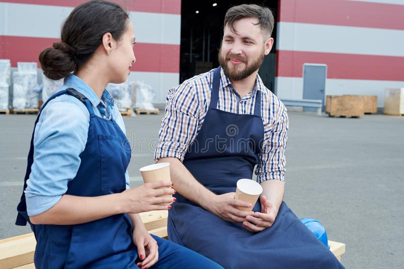 Two Workers on Coffee Break. Portrait of two modern factory workers on break outdoors, drinking coffee and chatting sitting on stack of wood and smiling royalty free stock photos