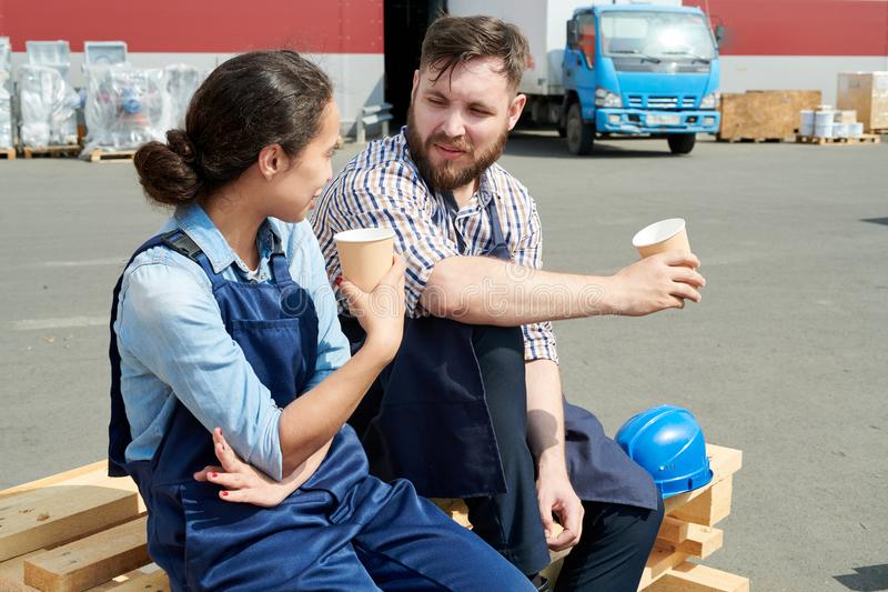 Workers on Break. Portrait of two modern factory workers on break outdoors, drinking coffee and chatting sitting on stack of wood in sunlight stock photos