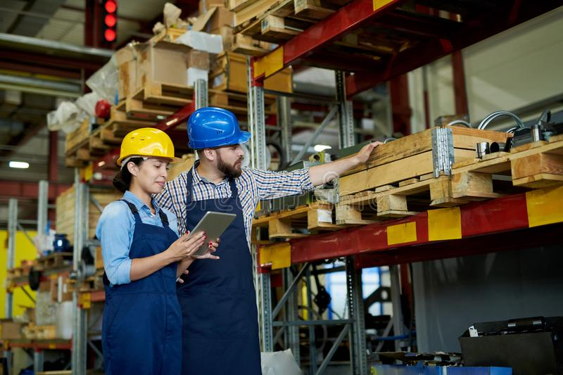 Stock Inventory at Plant. Portrait of two modern factory workers, men and woman, wearing hardhats doing inventory standing by shelves in warehouse, copy space royalty free stock image