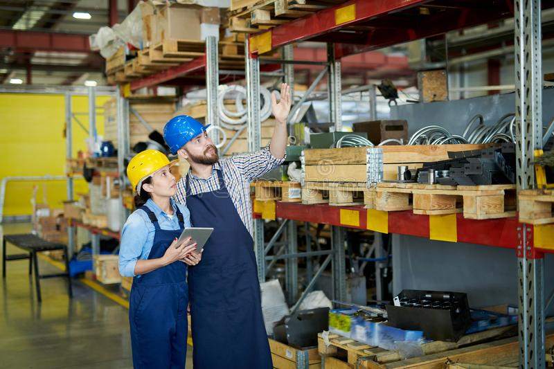 Warehouse Inventory. Portrait of two modern factory workers, men and woman, wearing hardhats doing inventory standing by tall shelves in warehouse pointing up royalty free stock photography