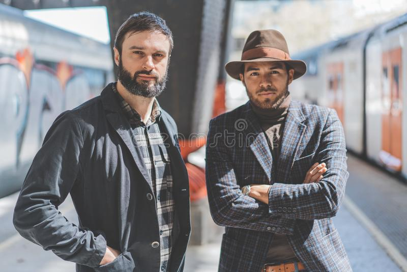 Portrait of two multi-ethnic bearded hipsters wearing together casual clothes and waiting the train on the railway. Platform royalty free stock images