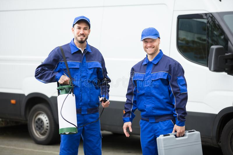 Portrait Of Two Pest Control Workers. Portrait Of Two Happy Male Pest Control Workers With Toolbox royalty free stock photo