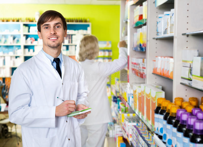 Portrait of two pharmacists working in modern farmacy. Portrait of two charming smiling pharmacists working in modern farmacy stock photos