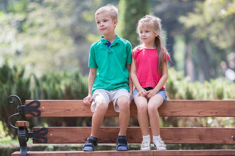 Portrait of two pretty cute children boy and girl having fun time on a bench in summer park outdoors royalty free stock photo