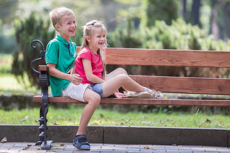Portrait of two pretty cute children boy and girl having fun time on a bench in summer park outdoors stock photos