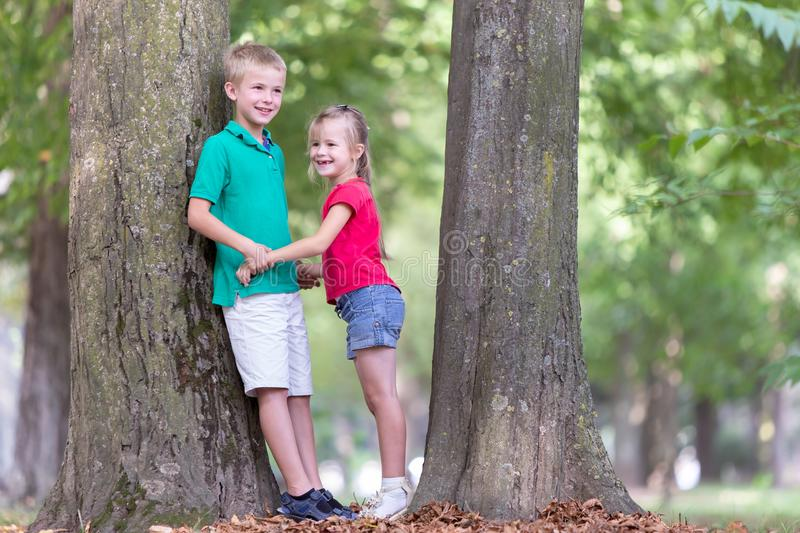 Portrait of two pretty cute children boy and girl standing near big tree trunk in summer park outdoors royalty free stock photos