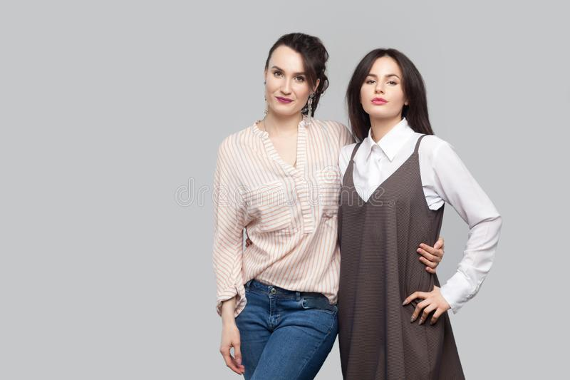 Portrait of two proud satisfied beautiful brunette best sisters in casual style standing, hugging each other and looking at camera stock image