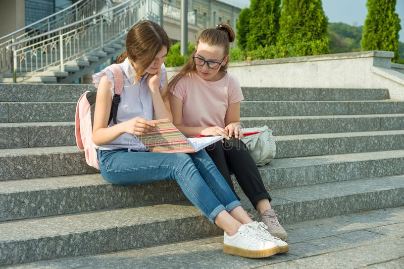 Portrait of two schoolgirls of teenagers with school backpacks and books. Talking, learning.  stock photos