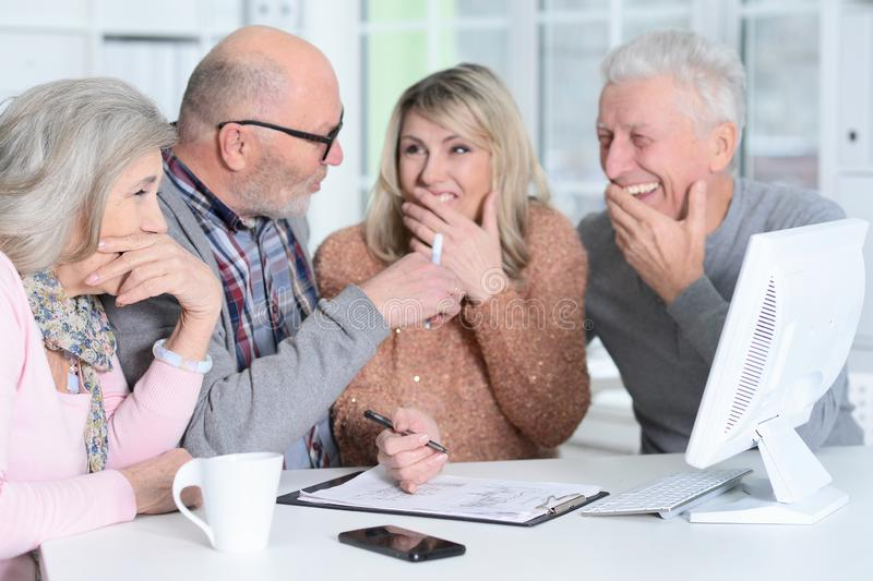 Portrait of two senior couples sitting at table and working. Two senior couples sitting at table and working with computer royalty free stock photo