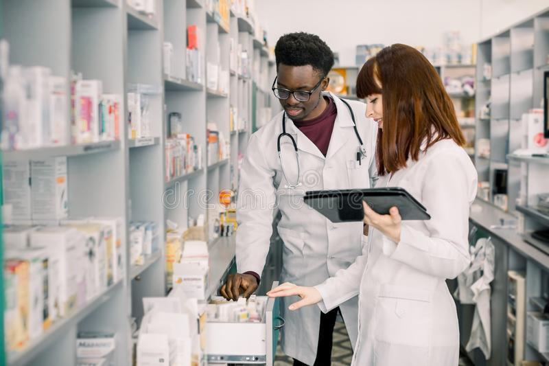 Portrait of two smiling friendly multiethnical pharmacists working in modern pharmacy and making order for medicines in stock image