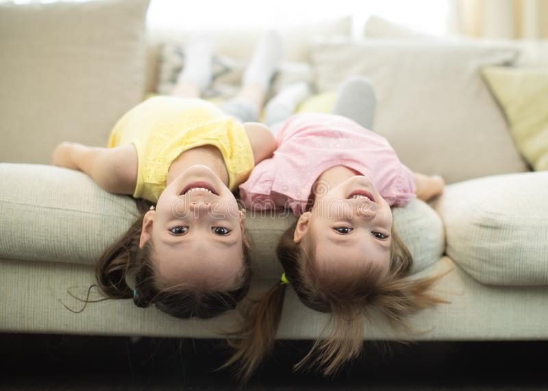 Portrait of two smiling kids sisters lying upside down on sofa in living room at home stock photos