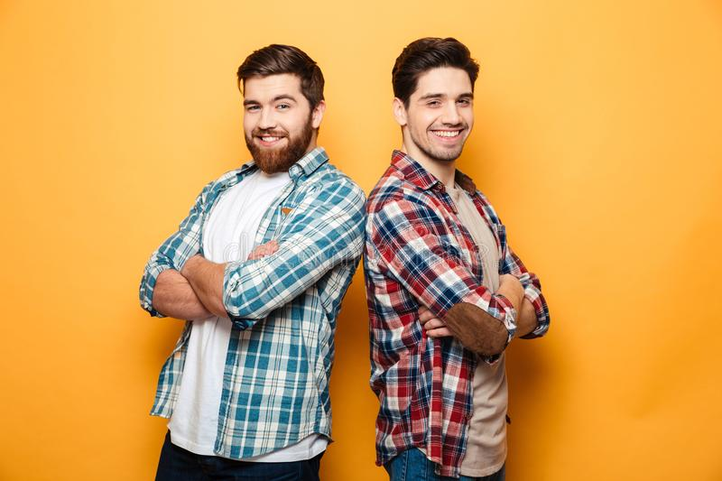 Portrait of a two smiling young men. Standing with arms folded back to back isolated over yellow background stock photo