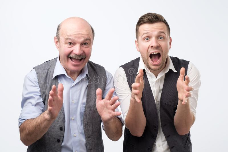 Portrait of a two surprised men father and son or best friends looking at camera with mouth open stock photo