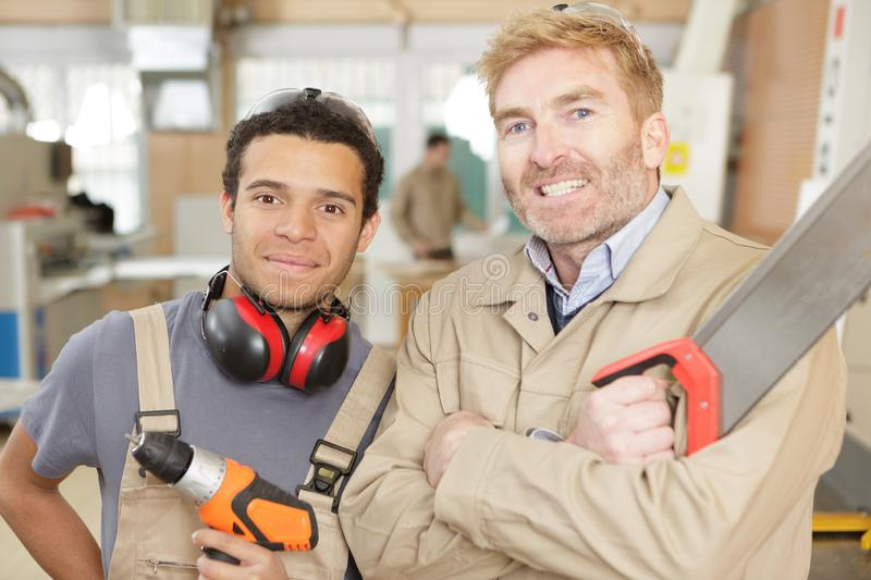 Portrait two tradesmen holding saw and drill. Portrait of two tradesmen holding saw and drill royalty free stock photo
