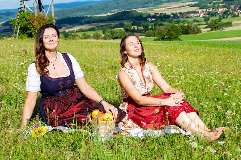 Two woman in dirndl sitting on blanket in meadow and enjoying the sun. Portrait of two women in dirndl sitting on blanket in meadow and enjoying the sun stock photos