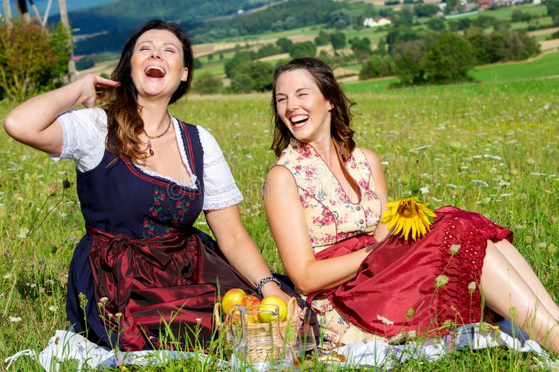 Two woman in dirndl sitting on blanket in meadow and laughing. Portrait of two women in dirndl sitting on blanket in meadow and laughing royalty free stock images
