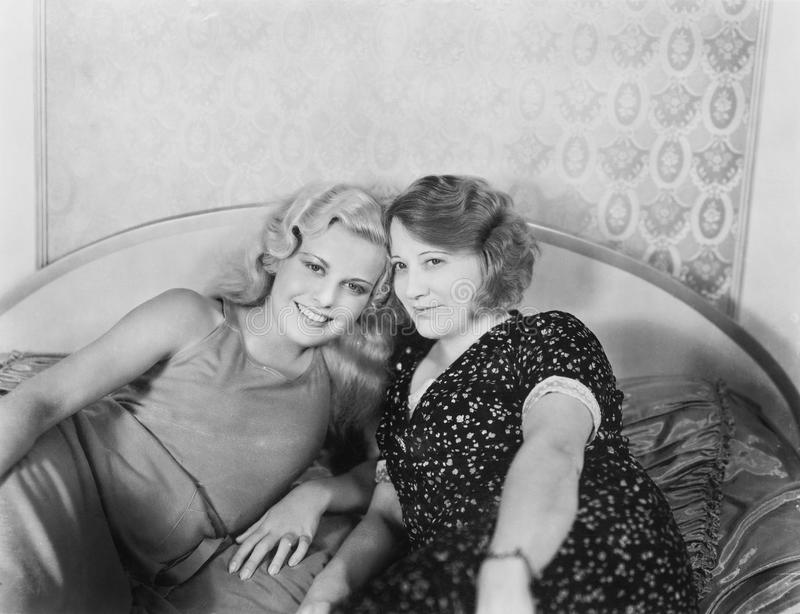 Portrait of two women lying on a bed. (All persons depicted are no longer living and no estate exists. Supplier grants that there will be no model release stock photos