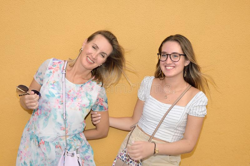 Portrait of two women with a yellow wall in the background stock photography