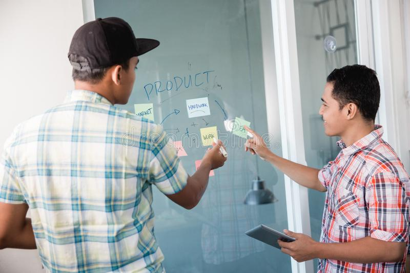 Portrait of two worker looks at paper notes on the wall and discuss about it. Portrait of two worker looks at paper notes on the wall and discuss about problem royalty free stock image