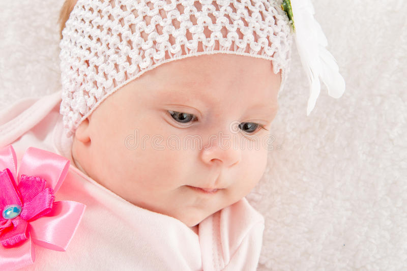 Portrait of a two-year baby girl with a bandage on his head with a flower. A two-month baby girl Europeans on the back with a bandage on his head with a flower stock photos