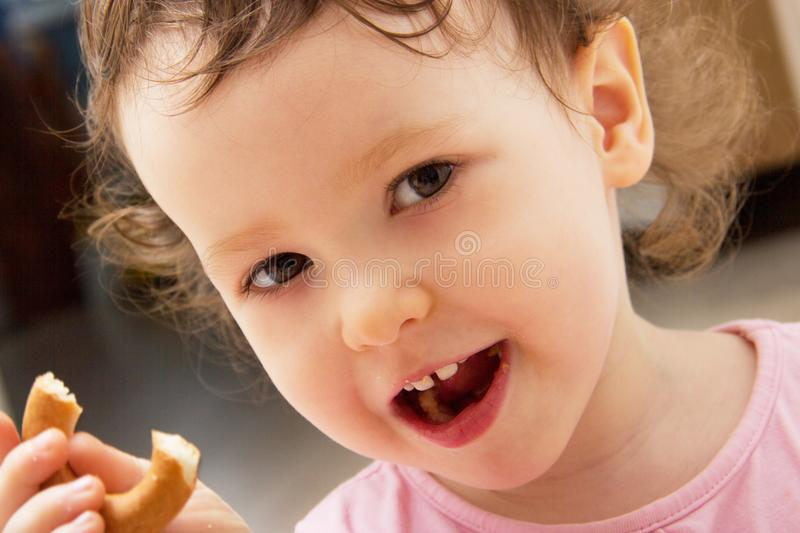 Portrait of a two year old baby girl. The curly child eats a bagel and smiles. Two front teeth are visible. Half-eaten bagel in ha royalty free stock photo