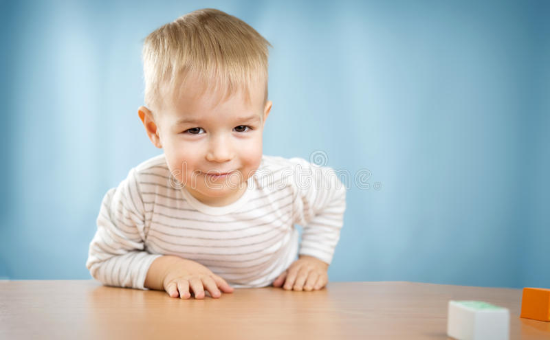 Portrait of a two years old child sitting at the table stock photos