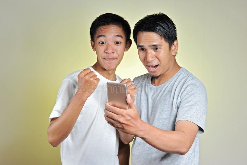 Portrait two young Asian men surprised, two young Asian men looking at cellphones screen. Amazed millennial guy received mail with stock photo