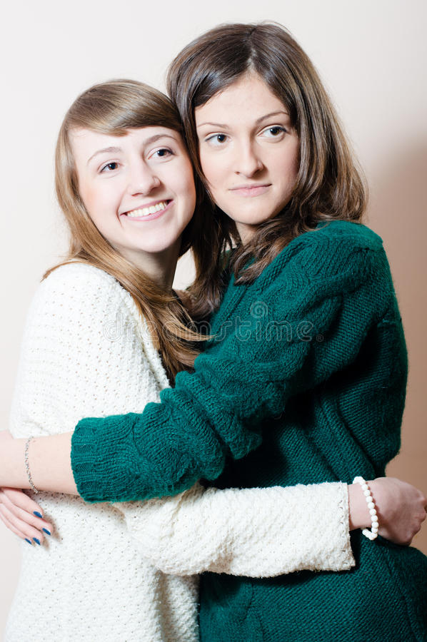 Portrait of two young attractive adorable women friendly hugging in knitwear royalty free stock photo