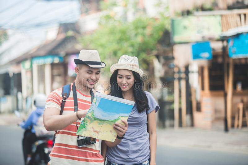 Two young backpackers searching direction on location map while. Portrait of two young backpackers searching direction on location map while traveling abroad in royalty free stock photos