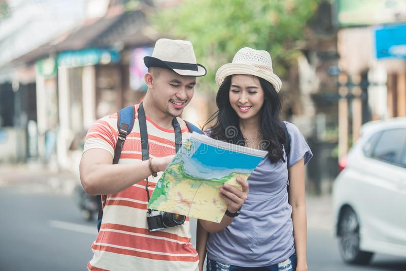 Two young backpackers searching direction on location map while. Portrait of two young backpackers searching direction on location map while traveling abroad in stock image
