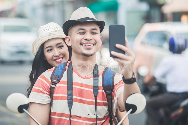Two young backpackers taking selfies using mobilephones camera w. Portrait of two young backpackers taking selfies using mobilephones camera while on motorbike royalty free stock image