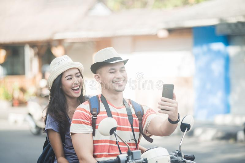 Two young backpackers taking selfies using mobilephones camera w. Portrait of two young backpackers taking selfies using mobilephones camera while on motorbike royalty free stock photo
