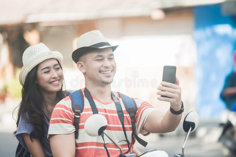 Two young backpackers taking selfies using mobilephones camera w. Portrait of two young backpackers taking selfies using mobilephones camera while on motorbike stock photos