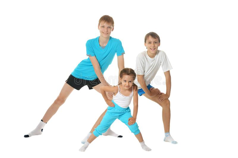 Portrait of two young boys brothers and little sister exercising isolated on white background royalty free stock image