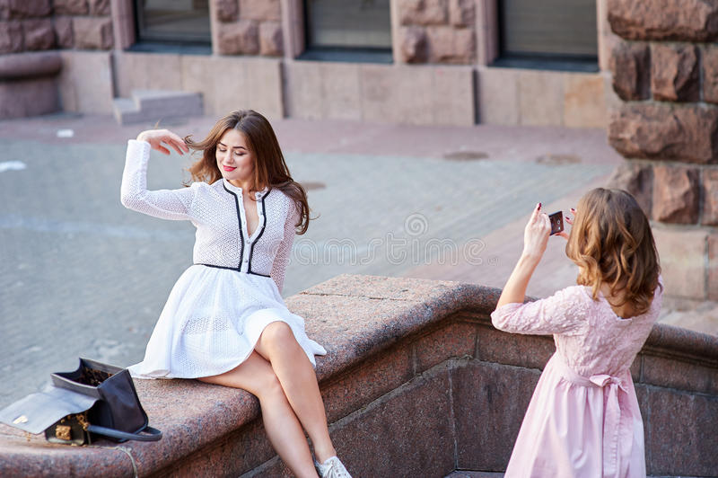 Portrait of two young girls taking pictures of themselves through cellphone stock photo