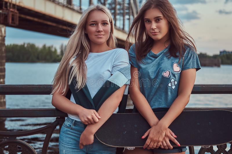 Portrait of a two young hipster girls holds a skateboard and leaning on a guardrail on a background of the old bridge. stock photo