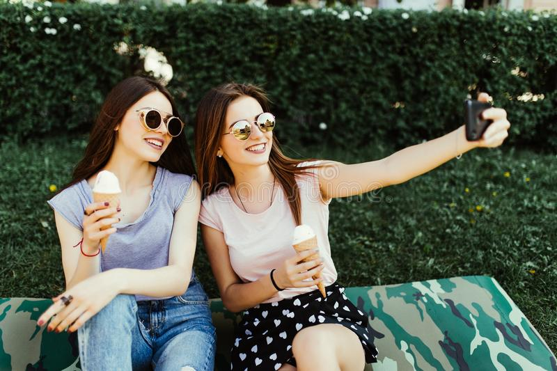 Portrait of two young pretty women standing together eating ice cream and taking selfie photo on camera in summer street. stock photography