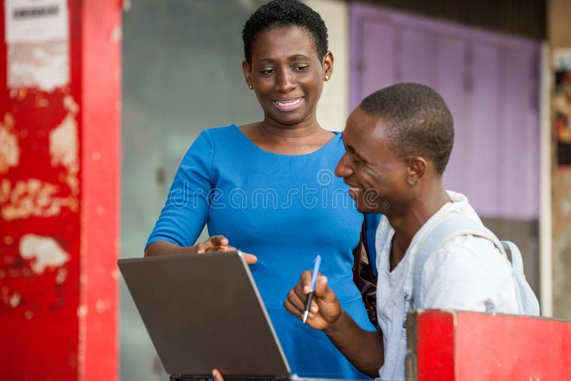 Two young students standing outdoors and discussing after school, Concept of Education. Portrait of two young students working a laptop and chatting outside on stock images