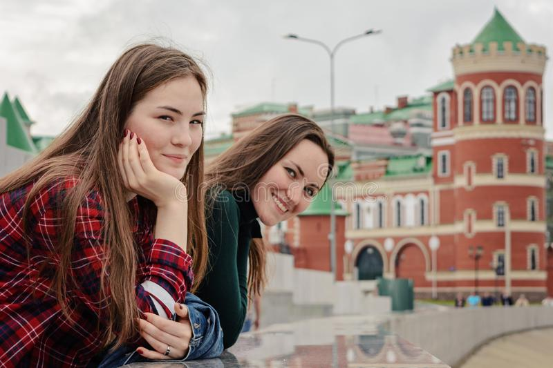 Portrait of two young women in casual wear on a walk around the city, standing and looking at the camera stock photos